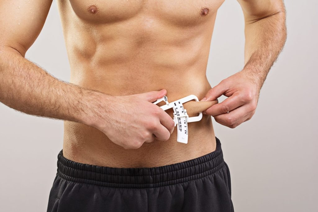 Fit sportsman measuring body fat with caliper
